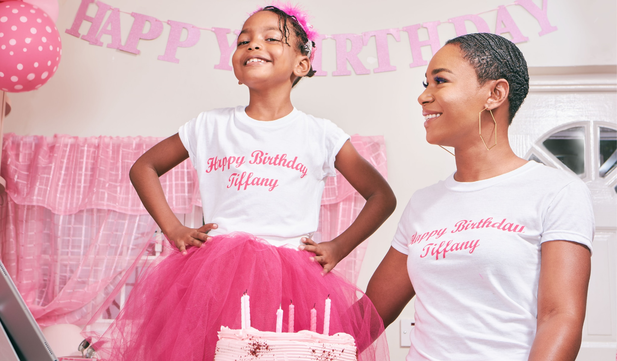 african american mother and daughter smiling with cake